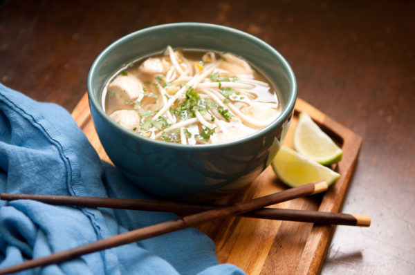 chicken pho in bowl with chopsticks and lime on wood background