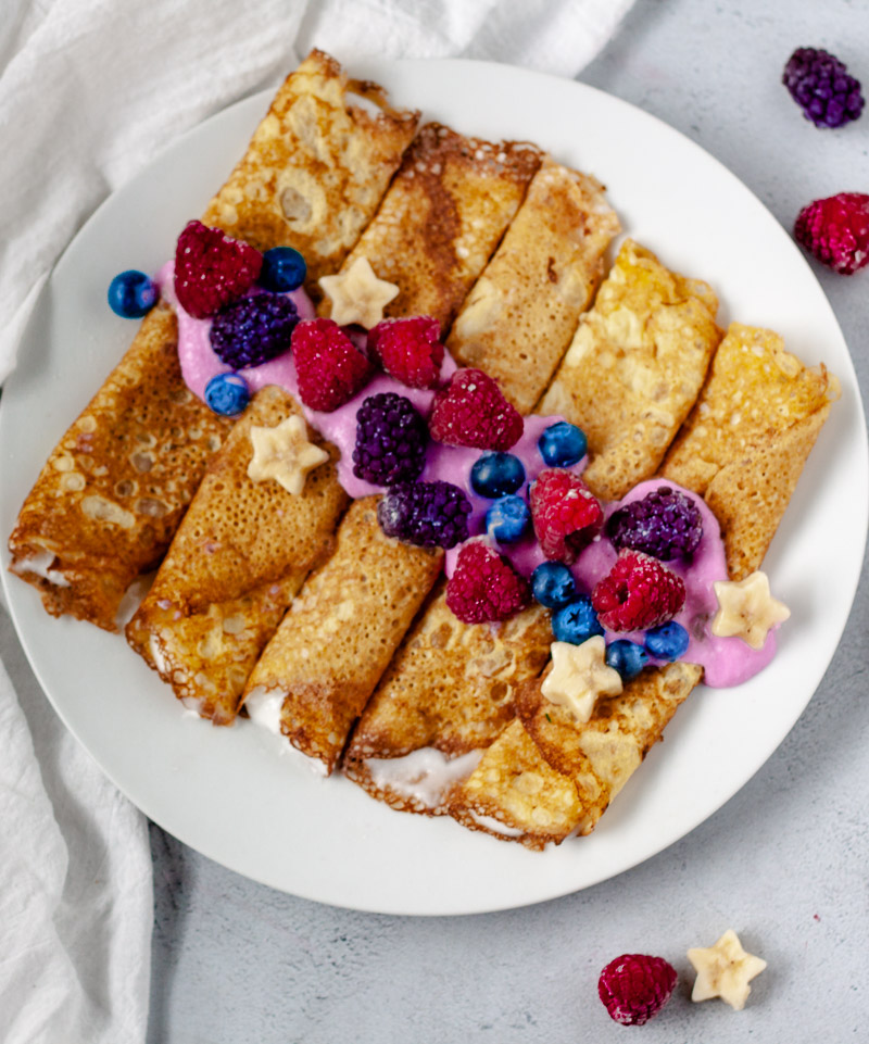 low-carb gluten-free crepes with yogurt and berries on white plate with white towel on grey background