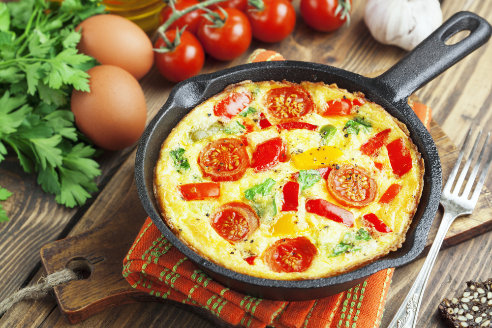 frittata with vegetables on wood background