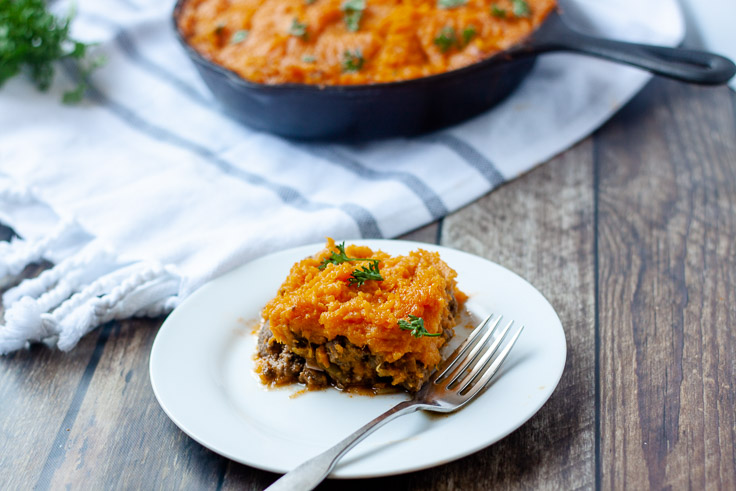 paleo sweet potato sheperds pie on white pan on wood background with white towel and skillet