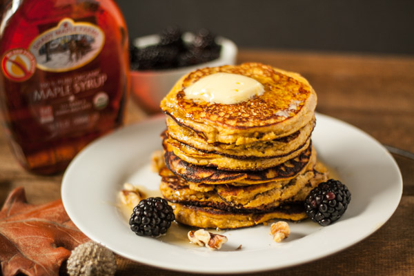 Paleo Pumpkin Pancakes Recipe, Paleo Pumpkin Pancakes on white plate with berries and maple syrup on wood background