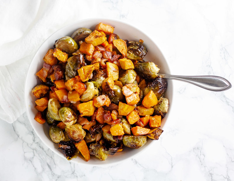 brussels sprouts with sweet potatoes and bacon in white bowl with spoon on white marble background
