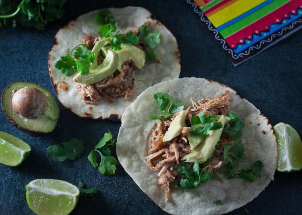 crock-pot chicken tacos, paleo crock-pot chicken tacos with avocado, limes, cilantro on grey baackground