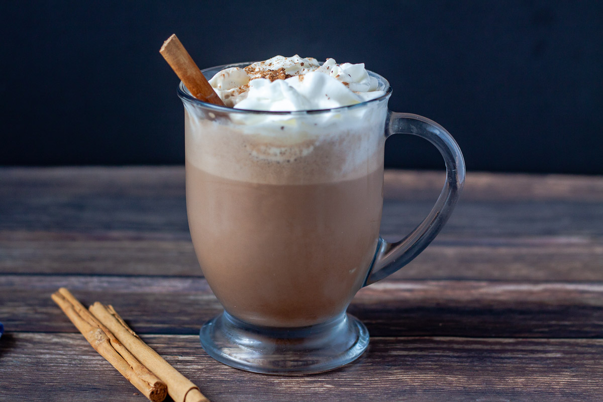 glass cup of hot chocolate with whipped cream and cinnamon sticks on wood background