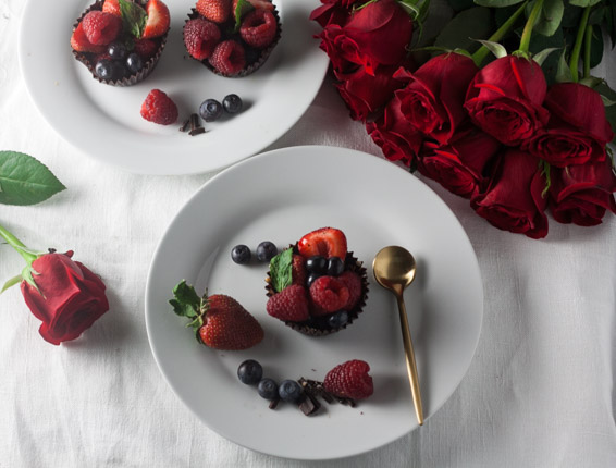 Dark Chocolate Berry Baskets on white plates with gold spoon, berries and red roses on white tablecloth
