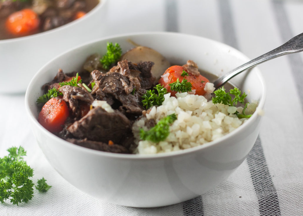 beef stew with bacon in white bowl on white striped towel with parsley