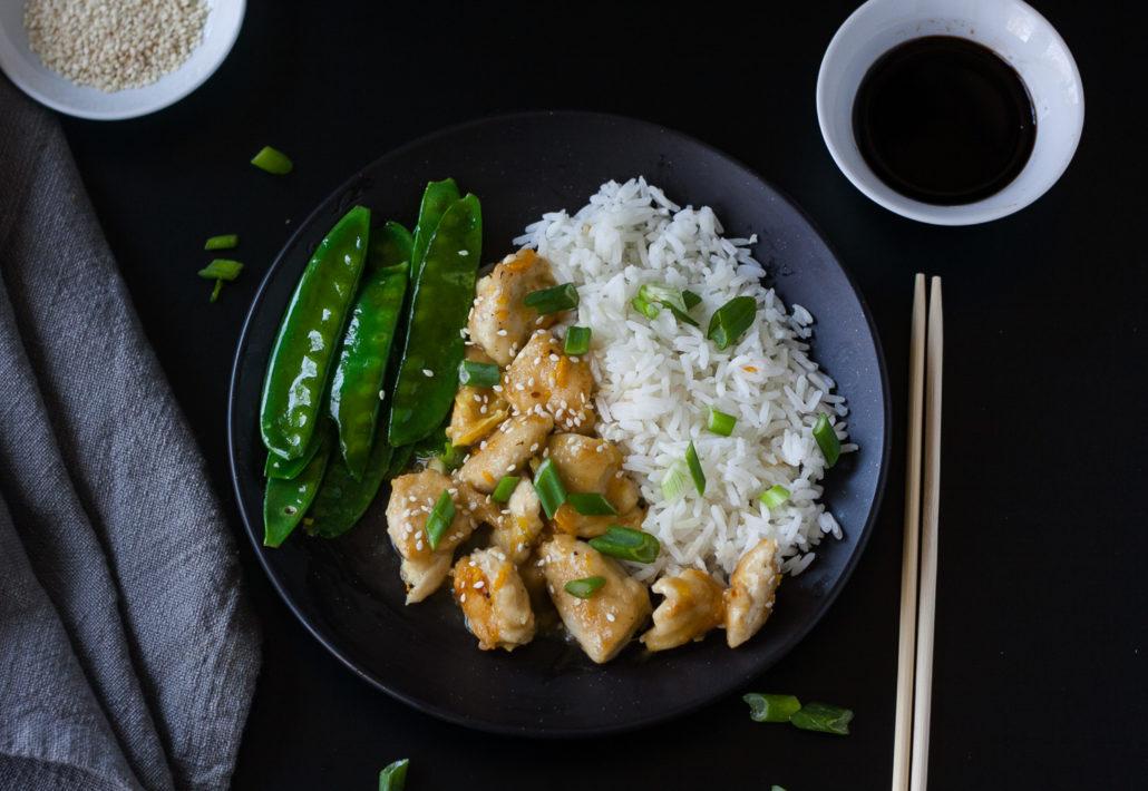 chinese orange chicken on black background with chopsticks