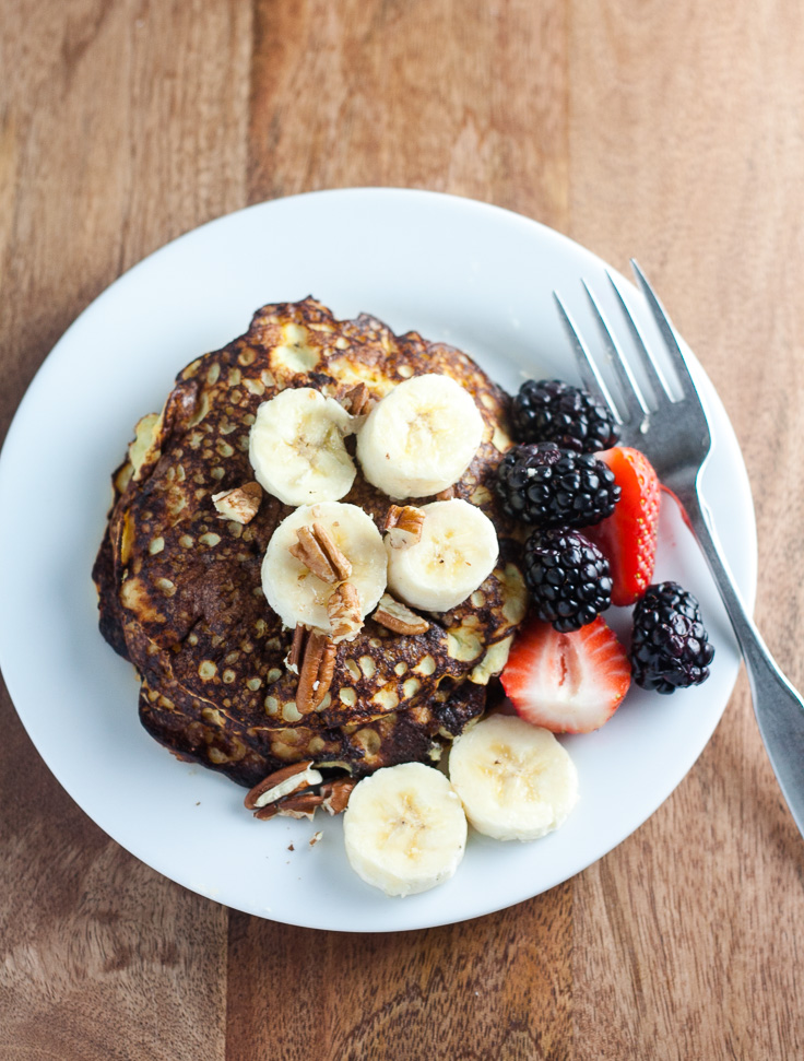 Stack of cultured banana pancakes topped with chopped bananas, berries, and chopped nuts on white plate with fork on wood background