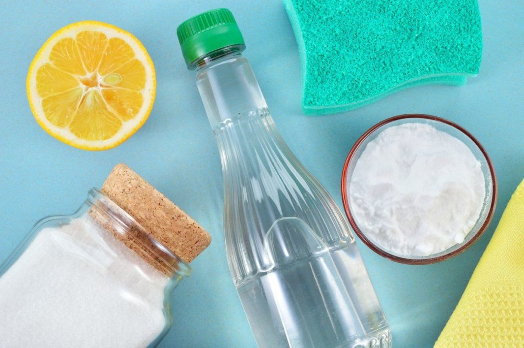Natural home cleaners vinegar, baking soda, salt, lemon with sponge and cloth on a blue background