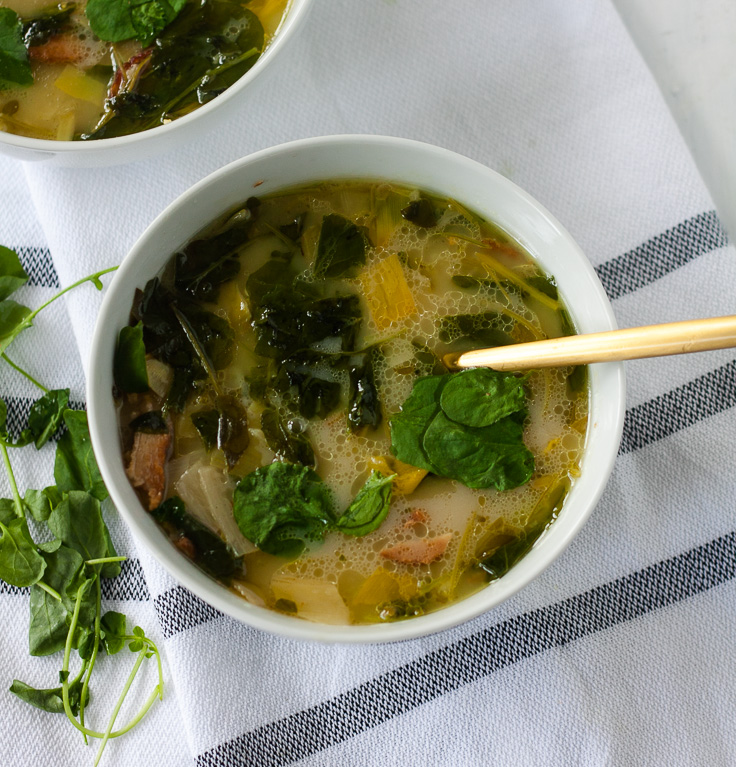 bowl of watercress bacon soup on white striped towel with gold spoon and watercress garnish