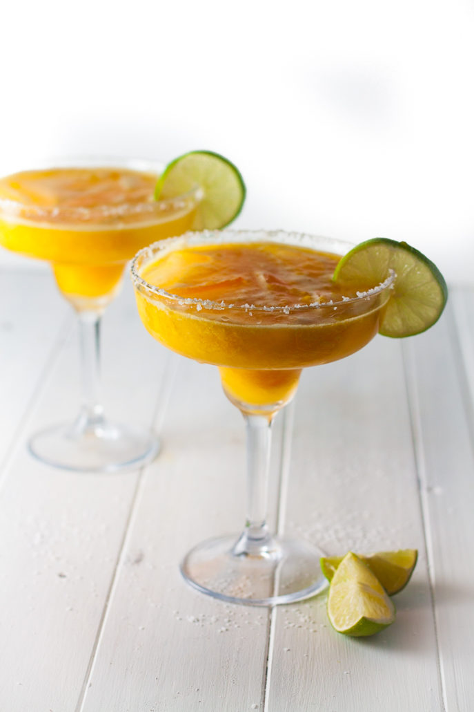 two mango margaritas with lime slices on white wood background