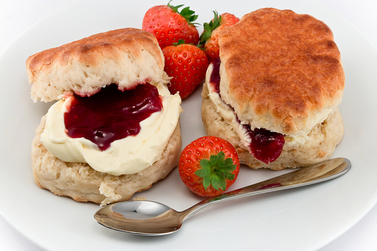 gluten-free english scones on white plate with clotted cream and jam, strawberries and spoon on white background