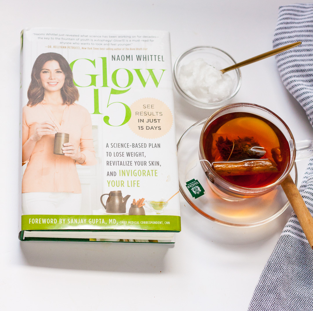 glow15 book with coconut oil and cup of tea with cinnamon stick and striped towel on white background
