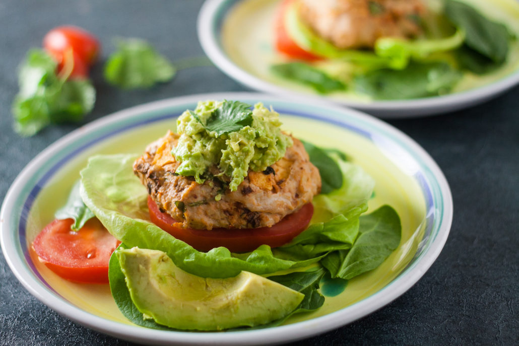 Turkey burgers on plate with lettuce, tomatoes, and avocados