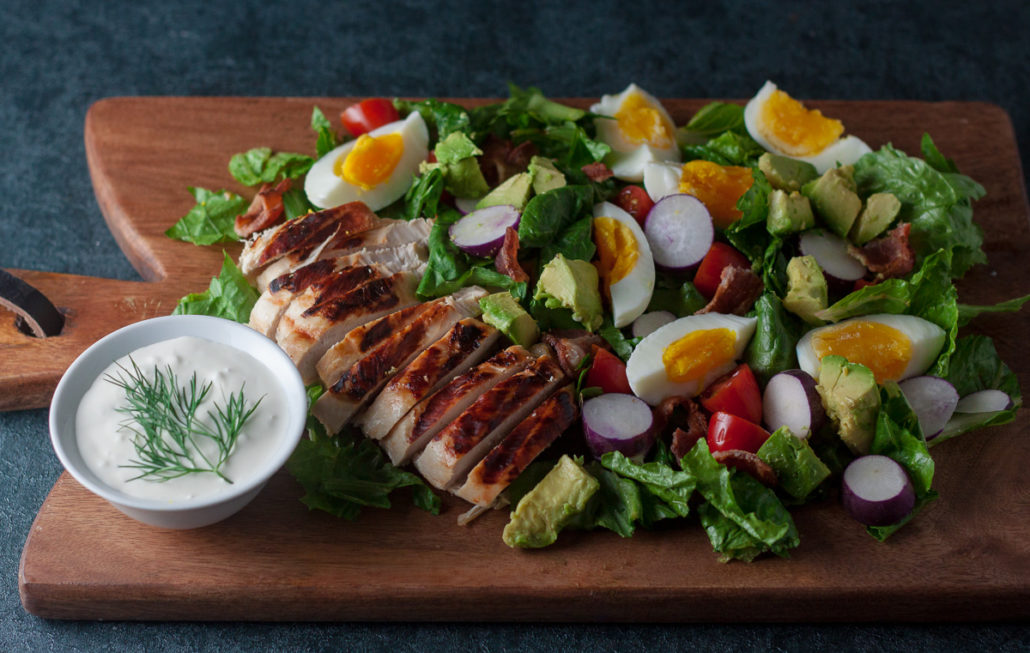 chicken cobb salad with ranch dressing on wood board