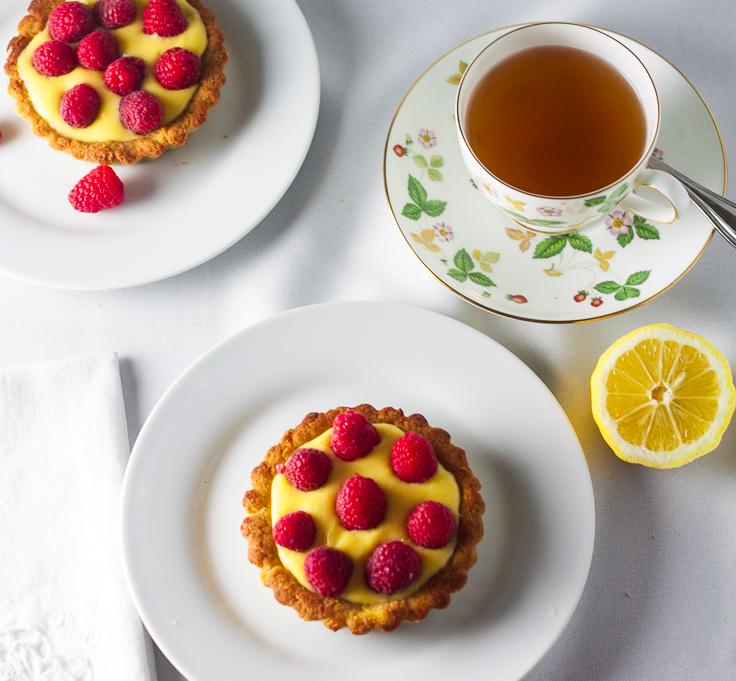 lemon tarts on white plates with cup of tea and lemon