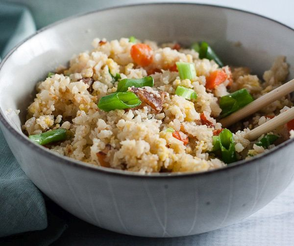 cauliflower fried rice in two bowls with chopsticks on grey background with green napkin