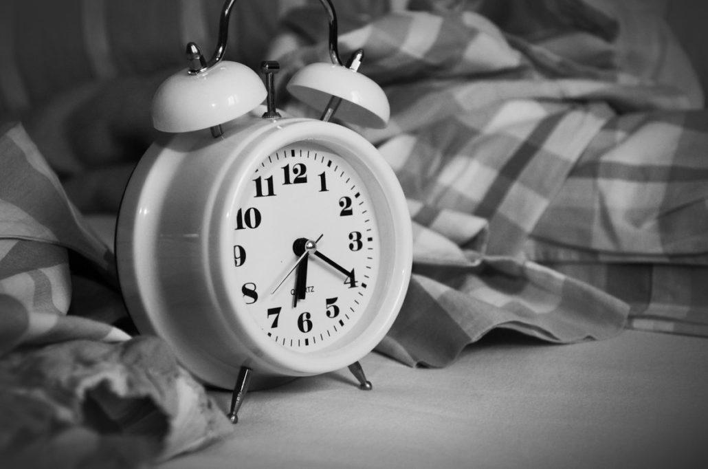 white alarm clock with grey fabric on grey background