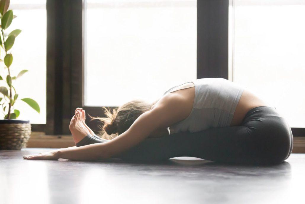 girl in seated forward bend yoga pose, aschimottanasana pose,wearing sportswear, grey pants, bra, indoor full length, home interior background