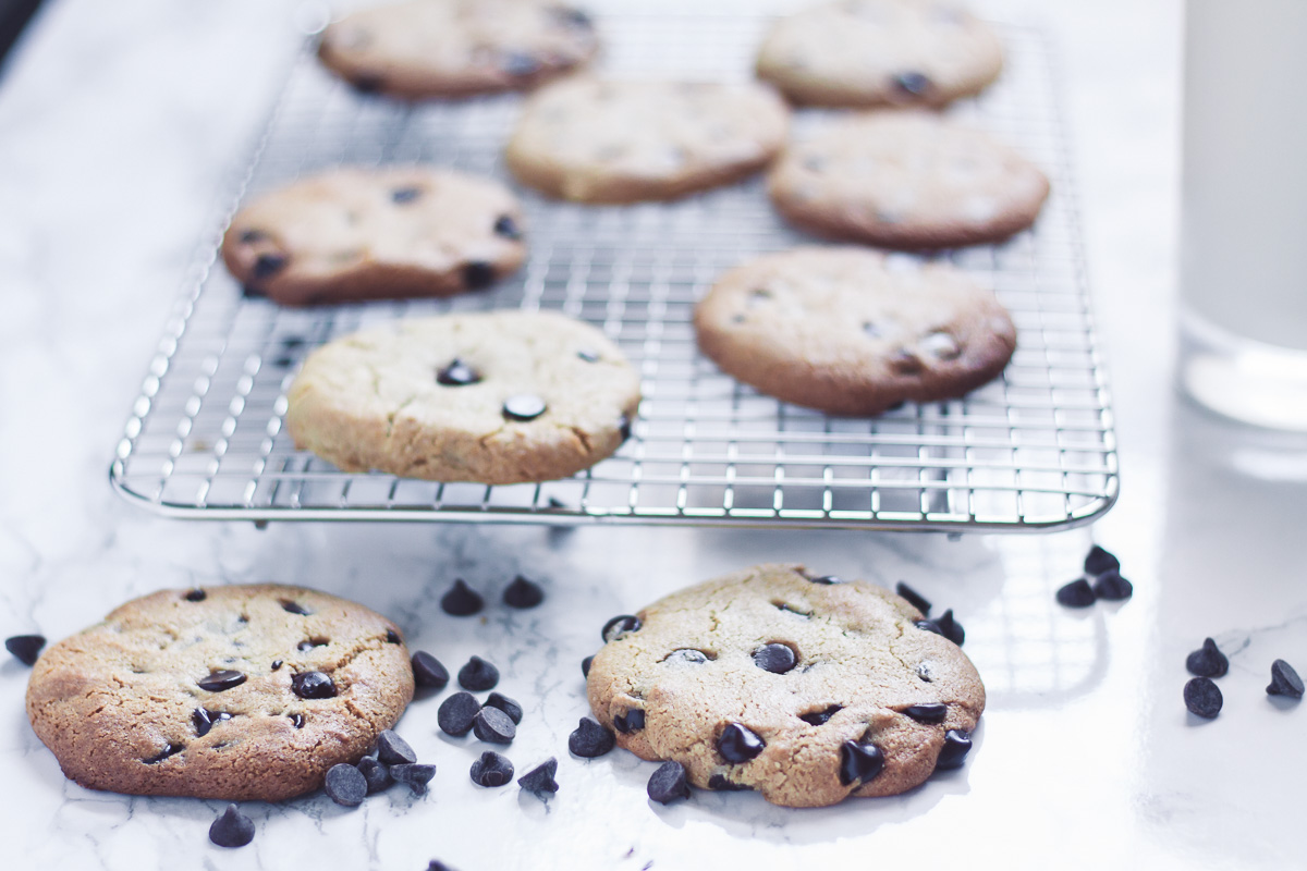 paleo chocolate chip cookies on silver baking tray with glass of milk and chocolate chips on white marble background