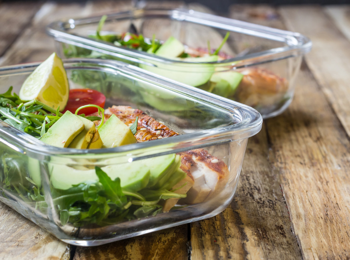 Healthy meal prep containers with arugula, turkey grill, tomatoes and avocado on wood background