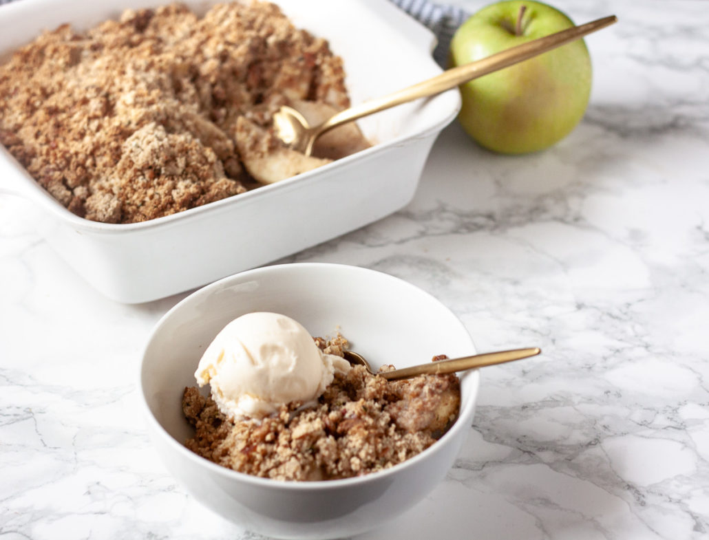 apple crisp topped with vanilla ice cream in white dishes on white marble background with gold spoons and green apple