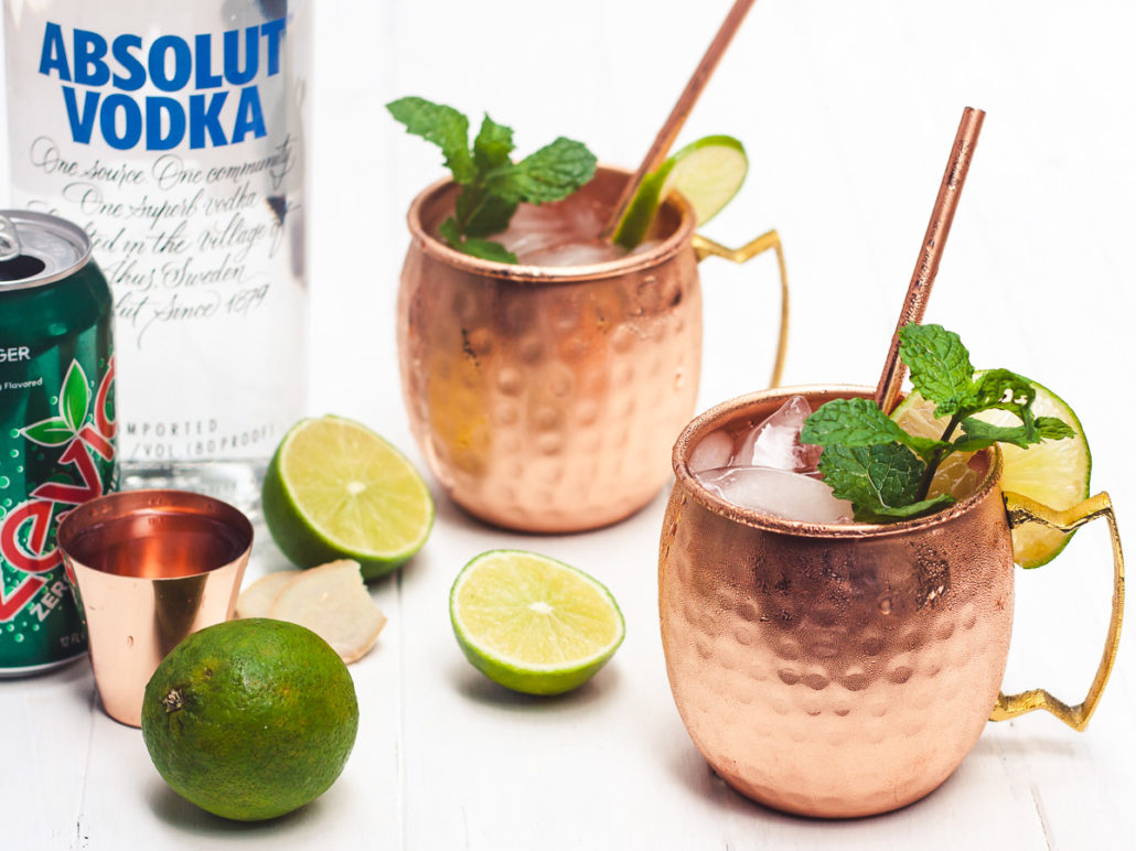 skinny moscow mules served in copper cups on white wood background with vodka, ginger beer, shot glass, limes and mint sprigs