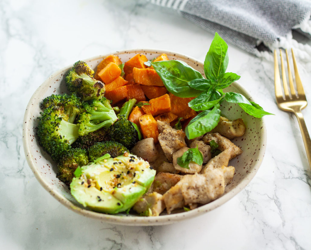 bowl with roasted broccoli, chicken, sweet potatoes, herbs and sliced avovado on marble background with grewy towel and gold fork