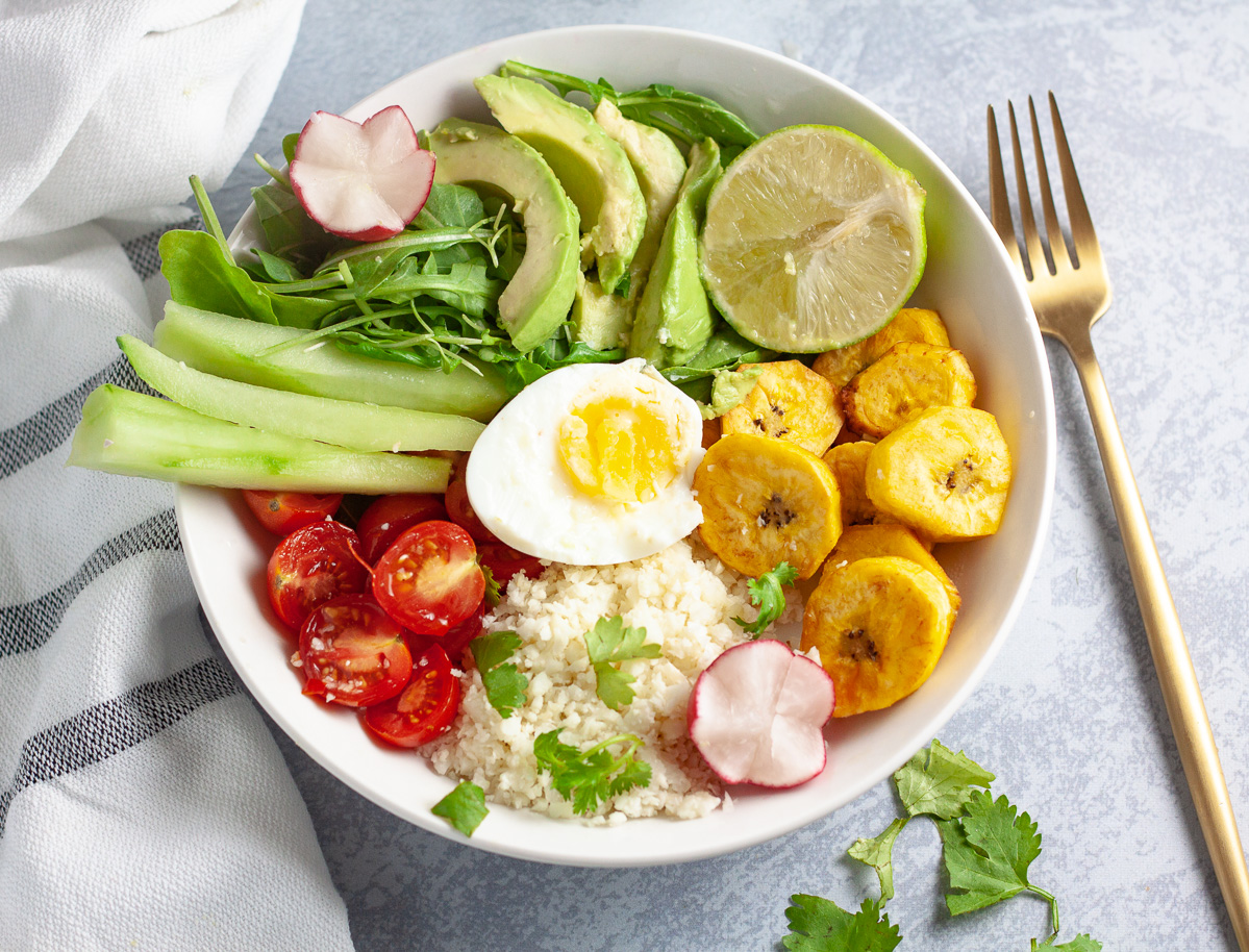 cauliflower rice buddha bowl with eggs, arugula, tomatoes, radish, lime, plantains, avocado and celery with white striped towel, gold fork and cilantro on grey background