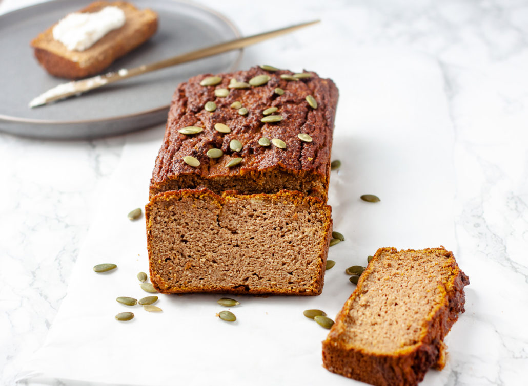 pumpkin bread on white marble backgrouond with grey plate and gold knife