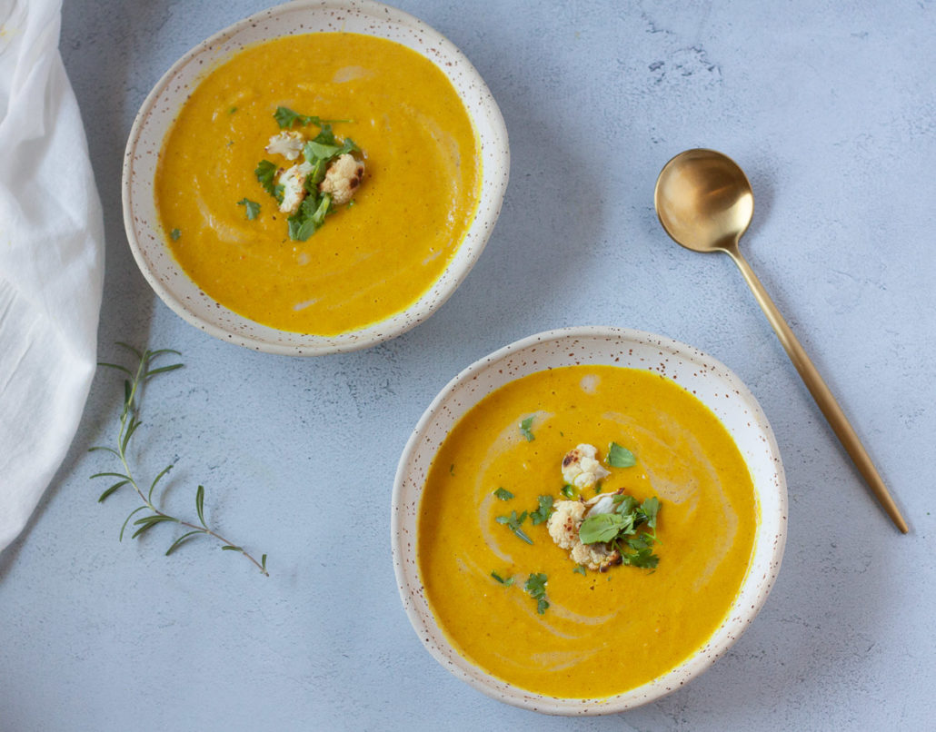 two bowls of roasted cauliflower soup with herbs and gold spoon on grey background