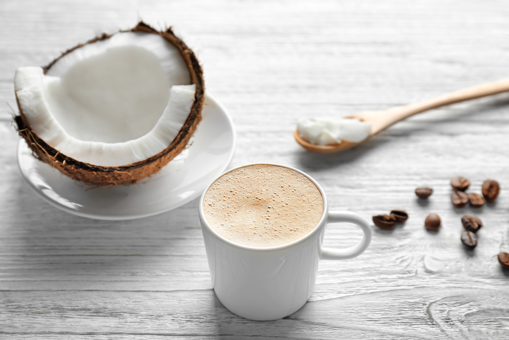keto diet coconut coffee in white mug with coconut coffee beans and spoon on white wood background