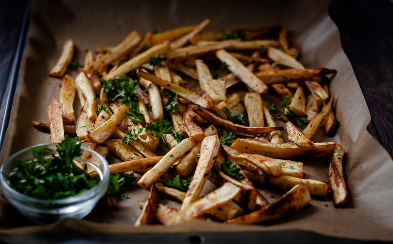 parsnip fries with herbs on baking sheet
