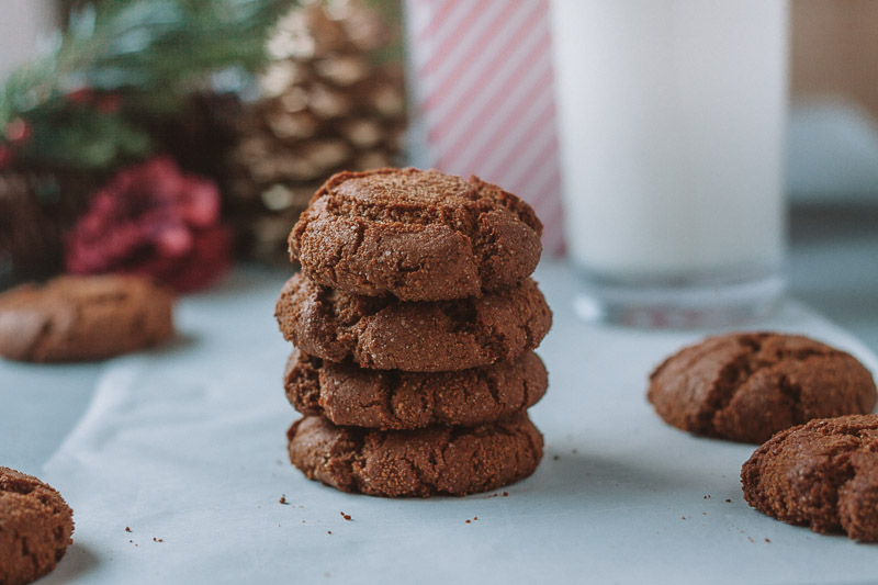 stack of paleo ginger snap cookies on white background with glass of milk and christmas ornaments