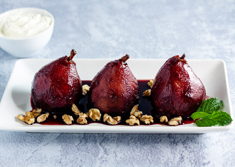 three poached pears in spiced red wine with walnuts and mint on white plate on blue background
