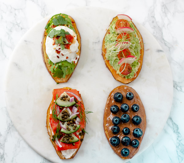 sweet potato toasts with various toppings on marble background