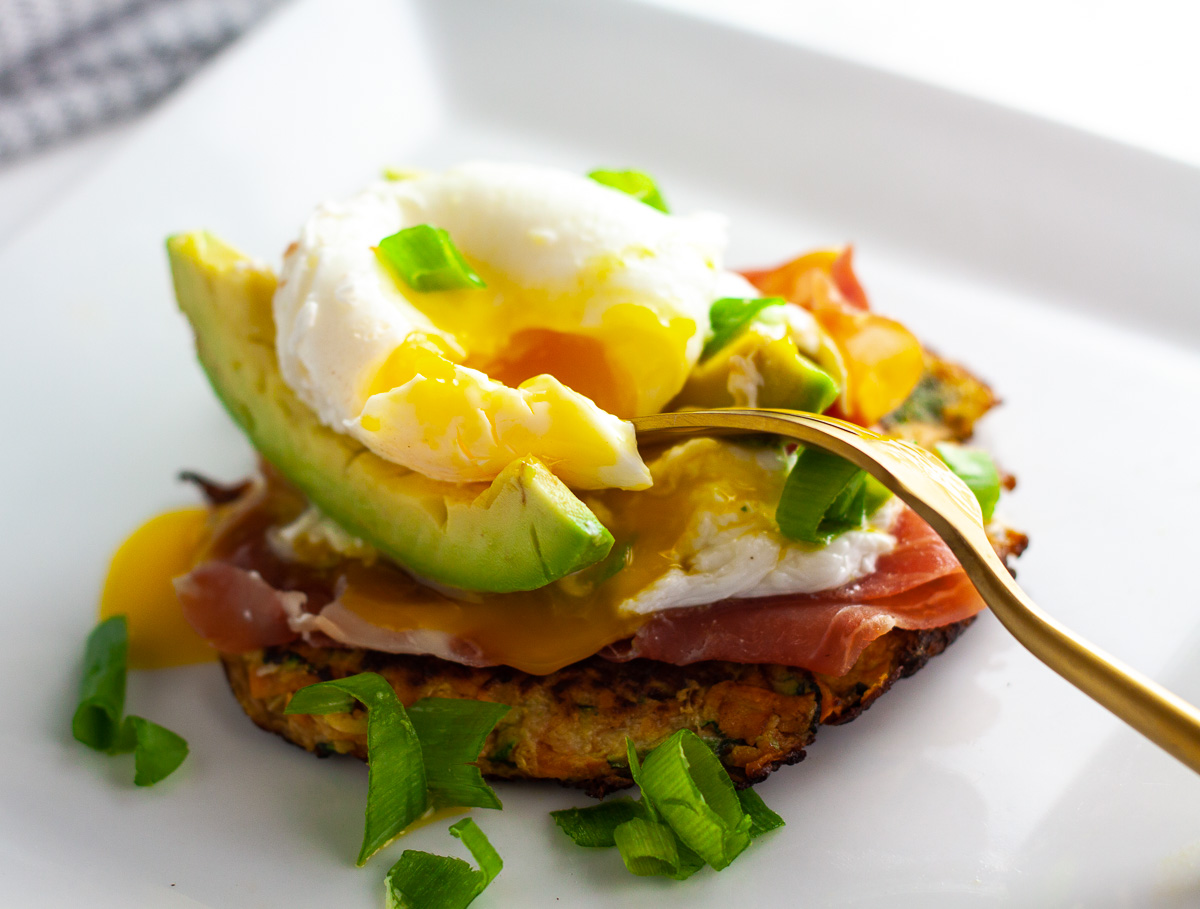 zucchini burger breakfast stack with zucchini burger, proscuitto, avocado, poached egg, green onions on white plate with gold fork