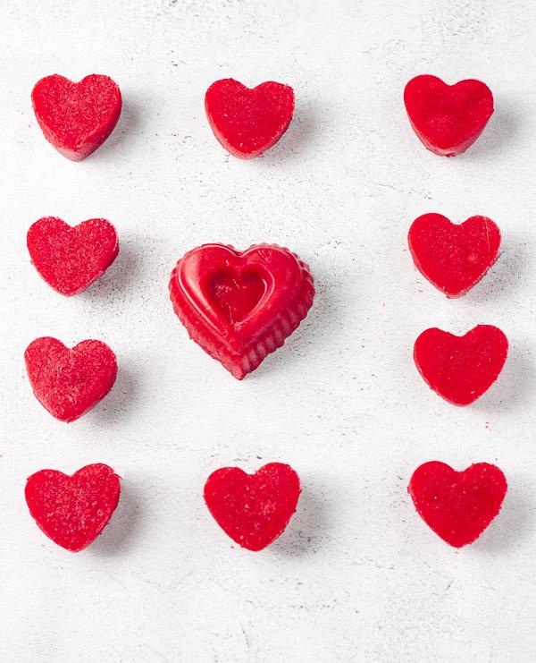 raspberry heart shaped gummies on grey background