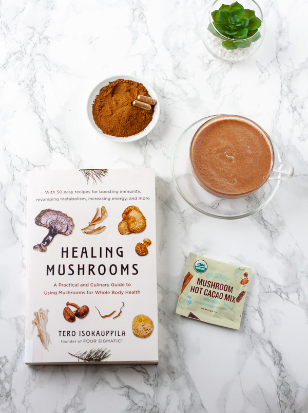 healing mushrooms book with resihi powder and mushroom hot chcolate on white marble background
