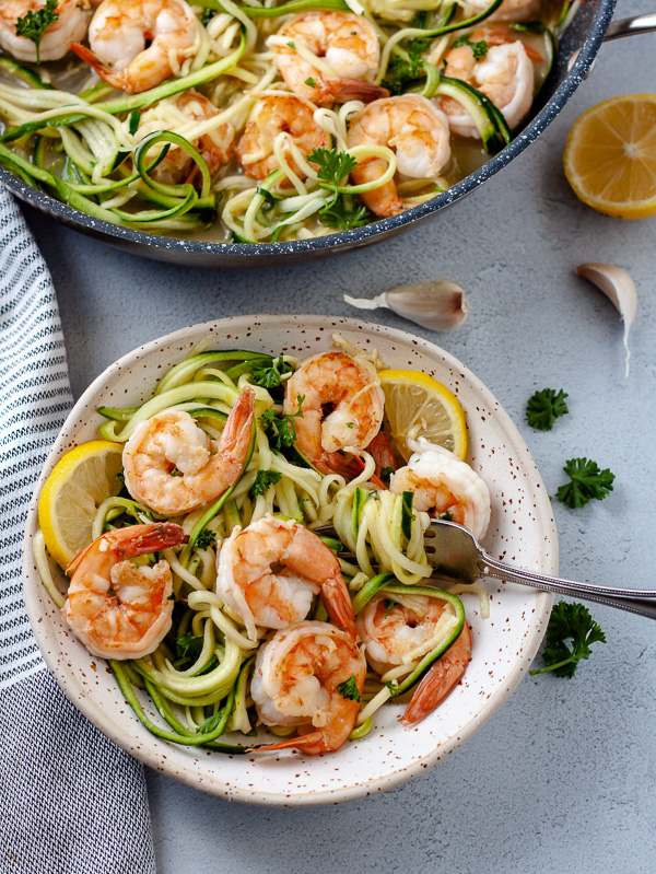 bowl of shrimp and zucchini noodles with lemon, garlic, and parsley with fork and pan on grey background