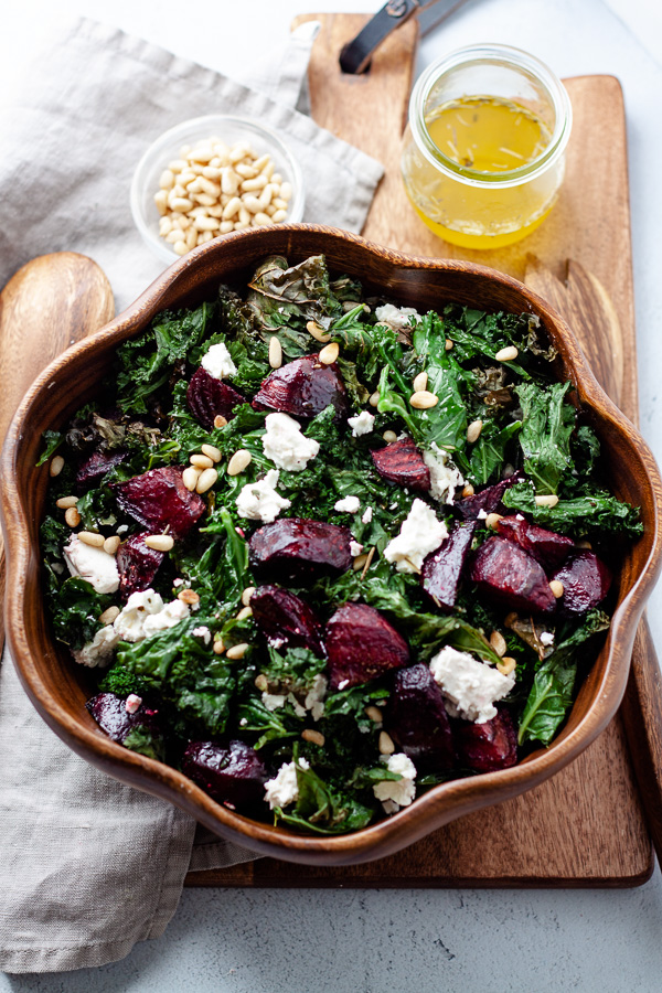 crispy beet and kale salad with feta cheese and pine nuts in wood salad bowl