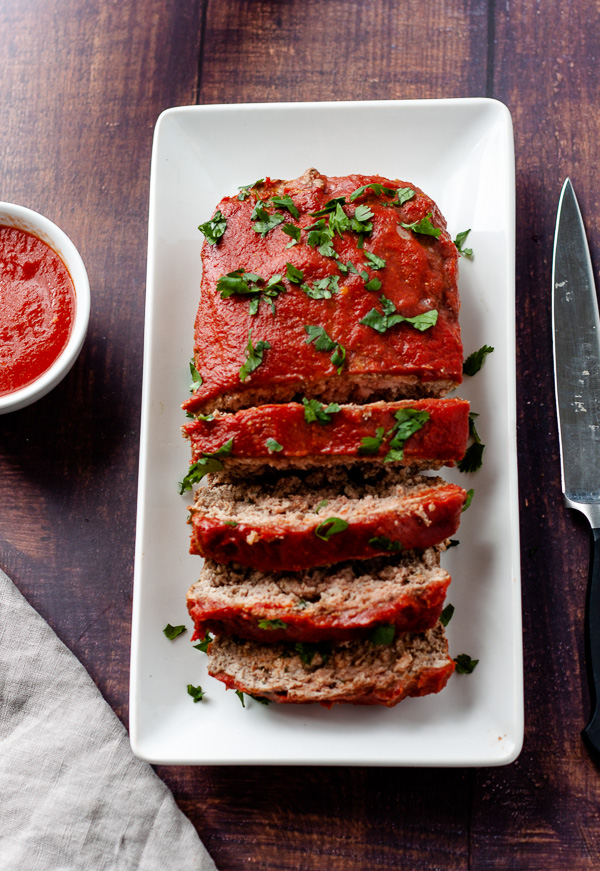 low-carb paleo meatloaf on white dish with knife and bowl of sauce and napkin on wood background