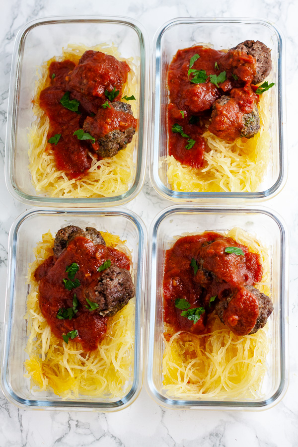 spaghetti squash and meatballs with marinara sauce in glass meal prep containers on white marble background