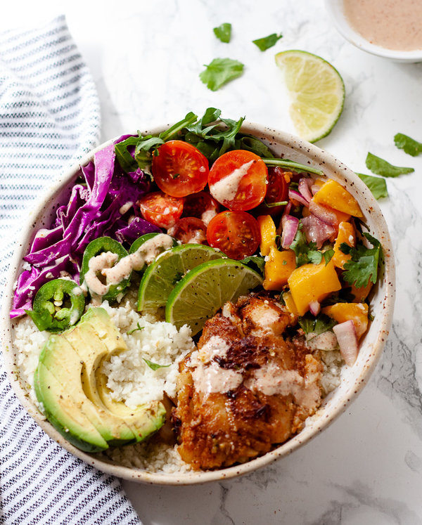 whole30 fish taco bowls with caulfilower rice and mango salsa in bowl on white marble background with lime and striped towel